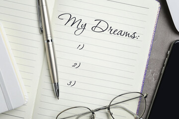 Notebook with dreams list on table, flat lay