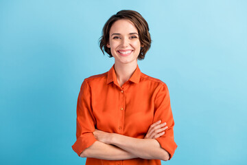 Fototapeta Photo of attractive bossy lady bobbed hairdo arms crossed self-confident person worker friendly smile white teeth good mood wear orange office shirt isolated blue color background obraz