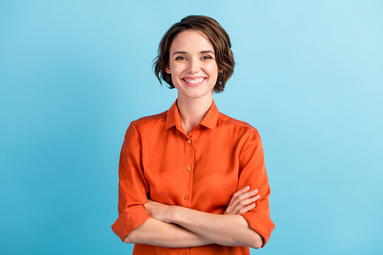 Photo of attractive bossy lady bobbed hairdo arms crossed self-confident person worker friendly smile white teeth good mood wear orange office shirt isolated blue color background