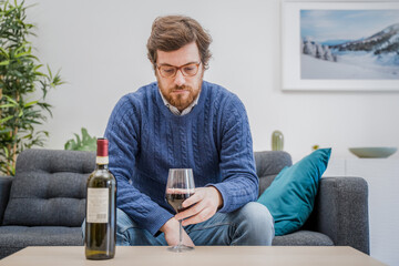 Portrait of man with alcohol drink sitting on sofa at home