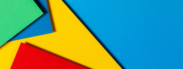 Abstract color papers geometry flat lay composition background with blue, yellow, green and red...