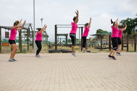 Group of woman performing jumping jacks exercise at boot camp