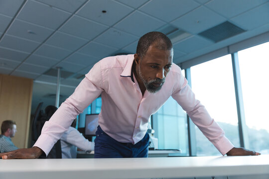Senior Black African American businessman leaning on table at modern office