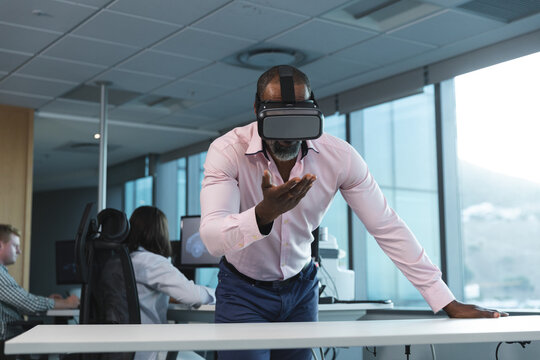 Senior businessman using virtual reality headset in modern office