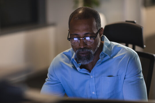 Black African American Senior businessman wearing glasses using computer in modern office