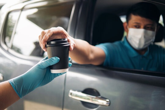 Drive thru food and drink service during Coronavirus COVID-19 pandemic. Staff hand in protective glove serving a coffee cup to customer a car driver man in protective face mask at drive thru service.