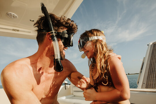 Smiling father and daughter in snorkel enjoying holiday on yacht