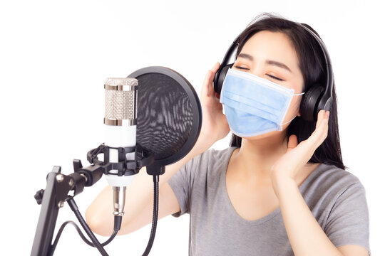 Portrait young asian woman recording song in a recording studio or Voice actor female dub and recording sound of some character of movie in a recording studio. She wear face mask. white background