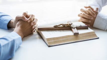 Christian woman praying with hands together on holy bible and wooden cross. Woman pray for god blessing to wishing have a better life and believe in goodness.