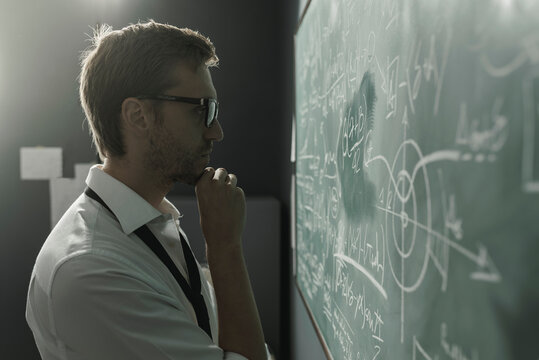 Young smart mathematician drawing on the chalkboard