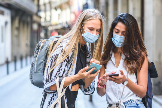 female tourists using mobile phone applications to guide themselves in the streets of a city. Concept of tourism in times of Covid19 pandemic