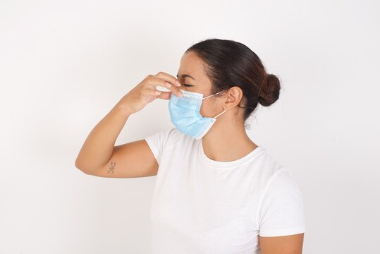 Young arab woman wearing medical mask standing over isolated white background smelling something stinky and disgusting, intolerable smell, holding breath with fingers on nose. Bad smell