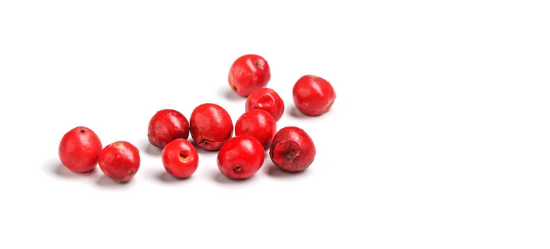 Red or pink peppercorns on board, closeup photo isolated with white background