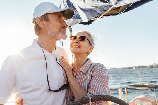Happy mature woman looking on her husband while he steering a yacht. Affectionate couple enjoying a vacation on private sailboat at sunny day.