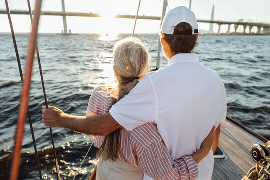 Back view of two mature people hugging together. Senior couple standing on a yacht bow and looking into distance.