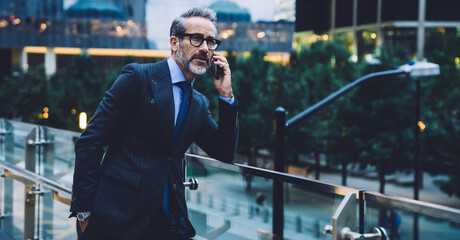 Adult businessman talking on phone against background of evening street