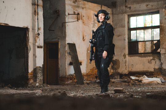 Portrait of young woman soldier in black uniform with an assault rifle.