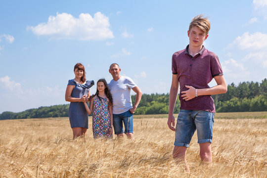 Handsome boy full length portrait with his father and preteen sister on background, Caucasian family in wheat field