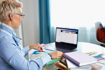 blonde caucasian female young school teacher using webcam at home, virtual teaching concept, giving...