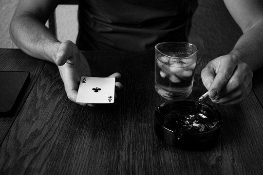 poker player with  aces in his hands and chips sitting at poker table in a dark room full smokes cigarettes
