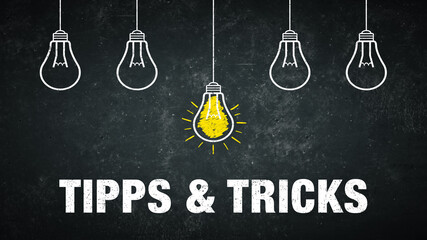 Tipps & Tricks. Text auf einer schwarzen Tafel mit Glühbirnen.