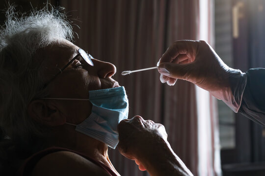 covid 19 swab nose test performed on elderly woman at her home