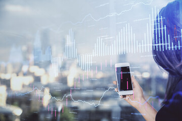 Double exposure of forex chart sketch hologram and woman holding and using a mobile device. Stock...
