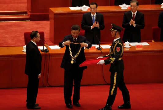 Chinese President Xi Jinping presents the national medal to respiratory disease expert Zhong Nanshan during a meeting to commend role models in China's fight against the coronavirus disease (COVID-19) outbreak, at the Great Hall of the People in Beijing