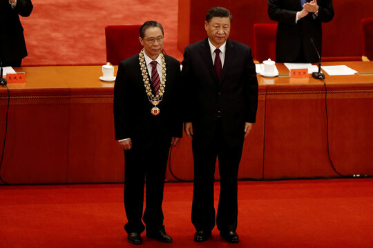 Chinese President Xi Jinping poses with respiratory disease expert Zhong Nanshan during a meeting at the Great Hall of the People in Beijing