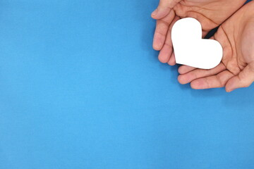 Male hands holding a white heart in blue background top view. Kindness, charity and compassion concept.