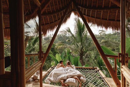 A hidden place. Sleeping couple wake up in the morning with nature view, couple lie in hammock, hug and kiss each other