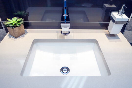 Modern bathroom white ceramic sink with chrom fixtures and plant