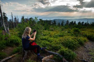 Fototapeta Kobieta robi zdjęcie telefonem w lesie na szczycie Turbacza obraz