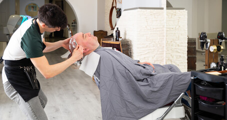 Young man barber shaving head for male client with sharp steel razor in barbershop