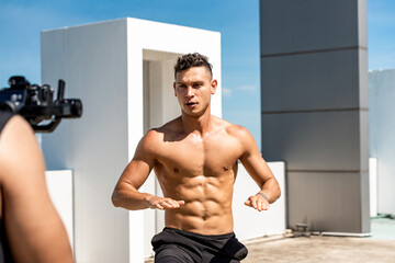 Muscular man fitness influencer recording exercise video clip ourdoors on rooftop, home workout...