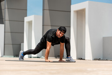 Fit handsome sports man warming up with spider lunge exercise outdoors on building rooftop floor