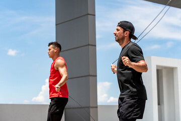 Two handsome Caucasian sportsmen doing morning outdoor jumping rope exercise on building rooftop