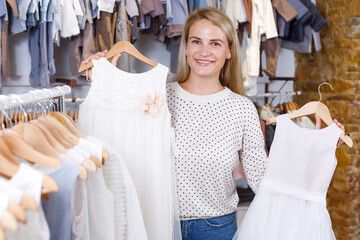 Positive young woman searching baby white dress in kids clothes store