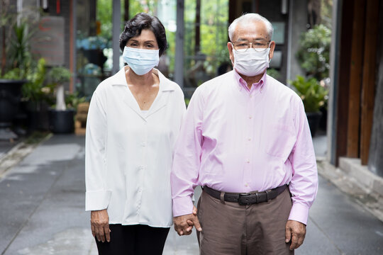 senior asian couple wearing face mask or face covering, concept social distancing, new normal lifestyle, protective health care