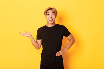 Portrait of happy and excited smiling asian guy holding something on hand over yellow background