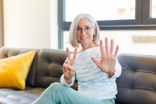 middle age pretty woman smiling and looking friendly, showing number seven or seventh with hand forward, counting down