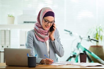 Beautiful young working woman in hijab and suit sitting in office, using smart phone. Portrait of confident muslim businesswoman. Modern light office with big window.