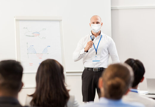 business, education and pandemic concept - businessman in mask for protection from virus disease with microphone and charts on whiteboard talking to group of people at conference presentation