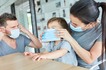 Eltern befestigen Mundschutz bei ihrem Sohn