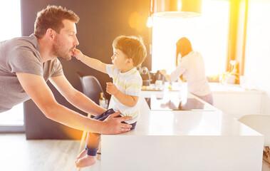 Vater spielt mit Kind in Küche zu Hause