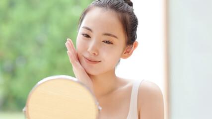 美容イメージ スキンケア お肌をチェックする日本人女性