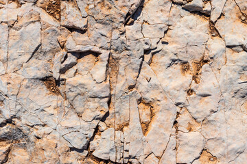 Background with a textured stone with cracks caused by the passage of time and in gray, white and brown colors