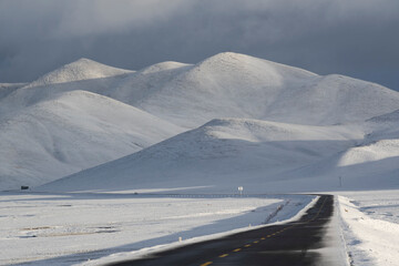 A road through a mountain landscape with snow