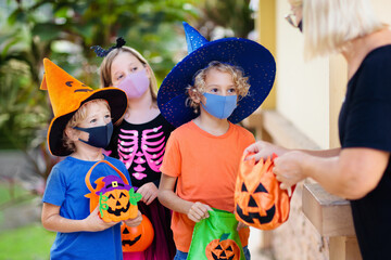 Kids trick or treat. Halloween in face mask.