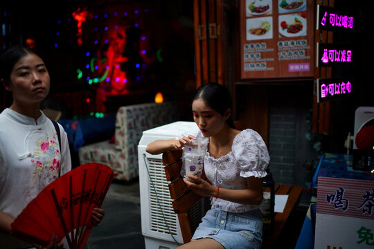 Woman holds her bubble tea at a restaurant on Jinli Ancient Street in Chengdu